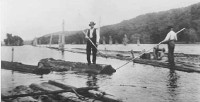 John Brennan, Boom Superintendent, with pike pole in hand, rides the last log to, and through the Gap of the St. Croix Boomsite at Stillwater. Famed photographer John Runk captured this moment in history on June 12, 1914 at precisely 2:30 that afternoon, one hundred years ago.